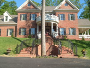 American Federal Home with curved wrought  iron railing  with  monkeys tails